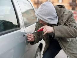 thief stealing insured car