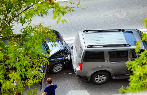 Collision of two cars with a man