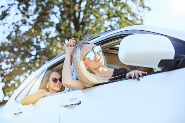 girls are taking a trip in their new car