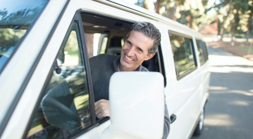 A happy vehicle owner after successfully paying his insurance premiums within the grace period.