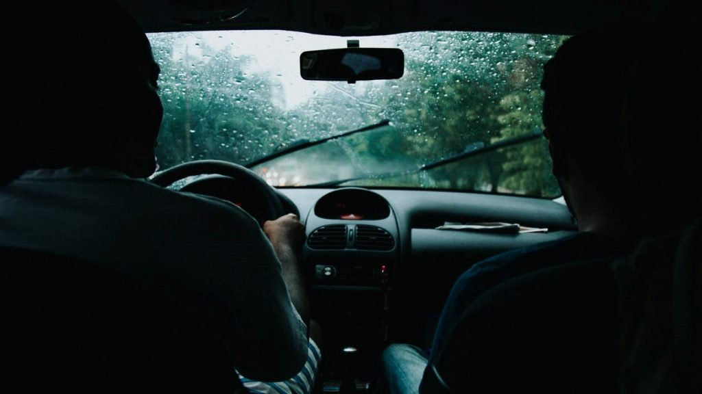 two people are driving during a heavy downpour