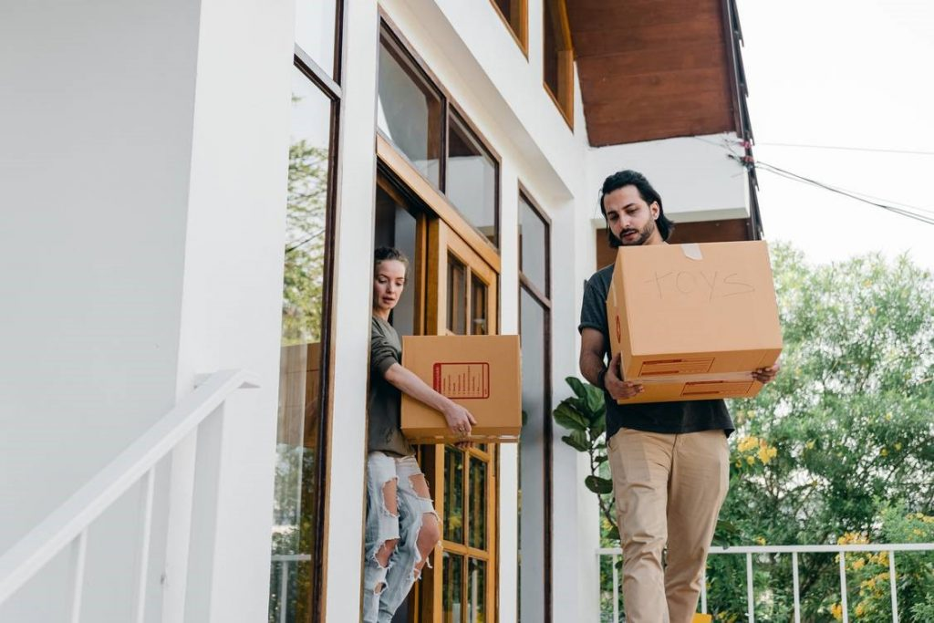 homeowners carrying two boxes out of the house