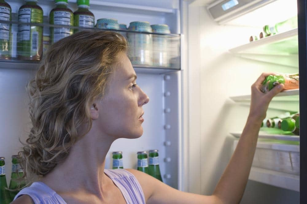 Women looking for food in the fridge.